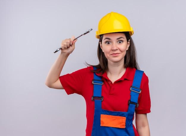 Jovem construtora surpresa segurando a chave da oficina e olhando para a câmera em um fundo branco isolado com espaço de cópia