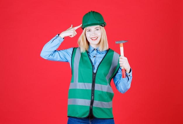 Jovem construtora usando uniforme verde e capacete segurando um martelo enquanto aponta uma arma para a cabeça na parede vermelha