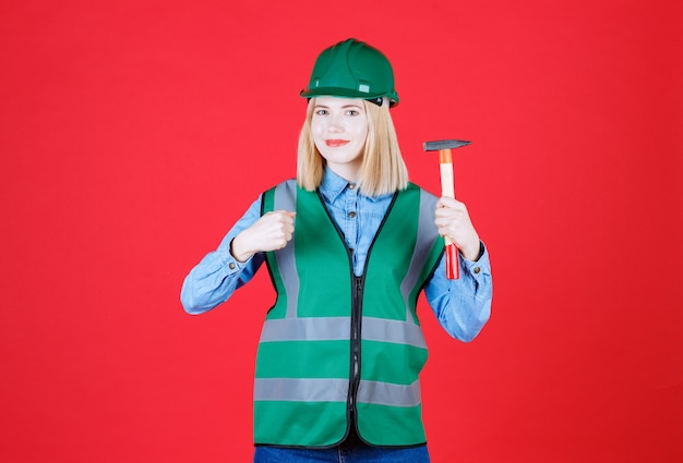 Jovem construtora vestindo uniforme verde e capacete segurando um martelo enquanto mostra o punho isolado no vermelho