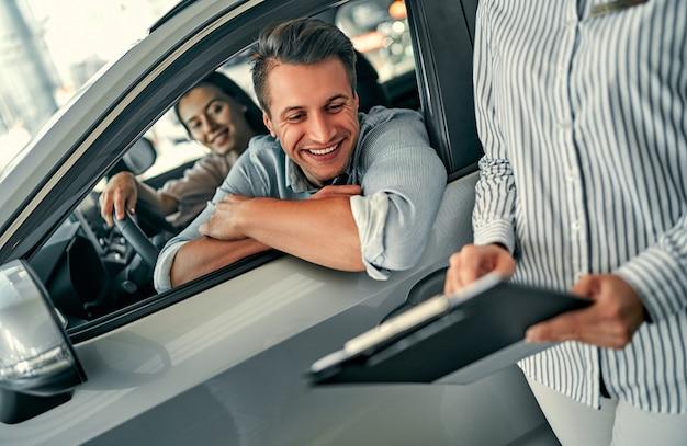 Jovem consultora e compradores de casal sentados no contrato de assinatura de carro novo no salão do automóvel. conceito de locação de veículos.