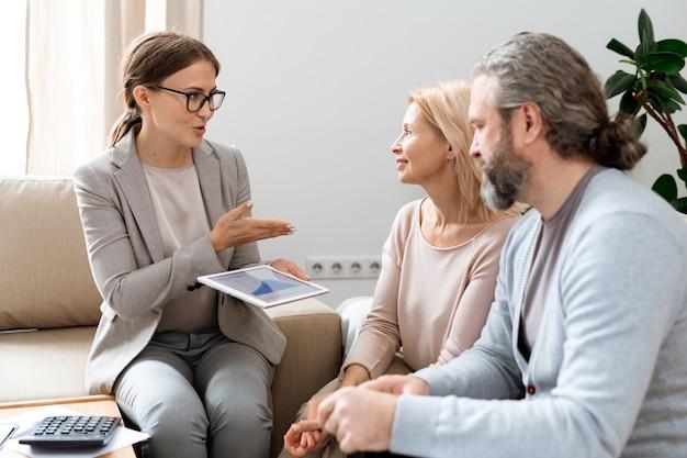 Jovem consultora imobiliária com tablet explicando os princípios de mudança de taxas de seus clientes na reunião
