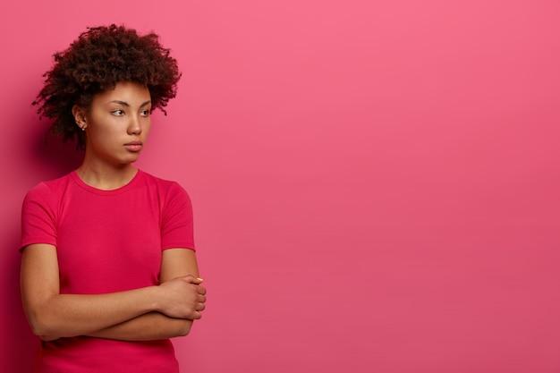 Jovem contemplativa mantém as mãos cruzadas, olha pensativo para o lado, tem cabelos cacheados, vestida com roupa casual, encosta na parede rosa, espaço vazio para suas informações promocionais.