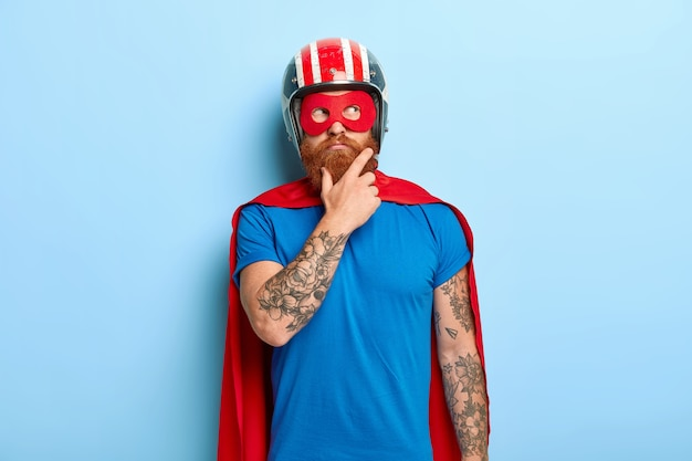 Jovem contemplativo barbudo com braços tatuados, pensa em voar, usa capacete