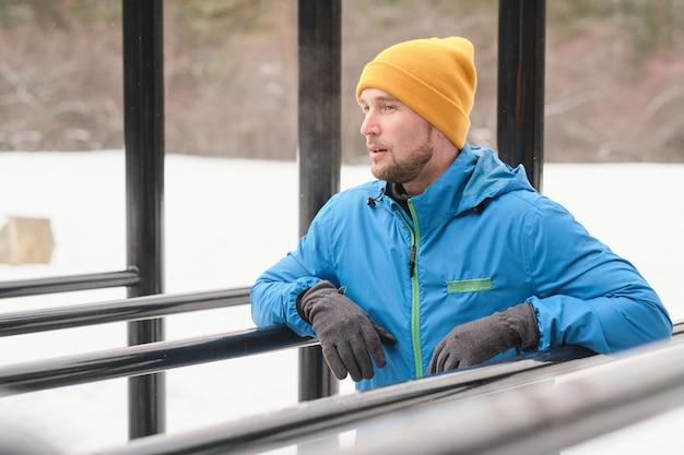 Jovem contemplativo com a barba por fazer nos ombros apoiados em barras paralelas enquanto descansa após se exercitar no inverno