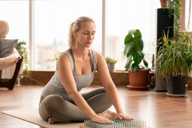 Jovem contemporânea em forma feminina em roupas esportivas, sentada na esteira com as palmas das mãos em almofadas de massagem de ioga durante exercícios de concentração