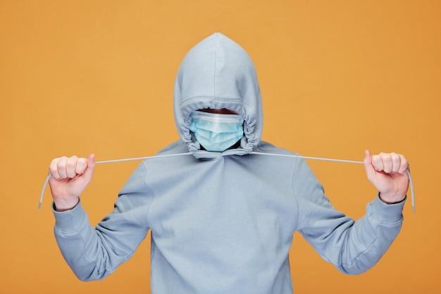 Jovem contemporâneo com capuz e máscara protetora esticando os cordões em pé na frente da câmera sobre a parede amarela Foto Premium