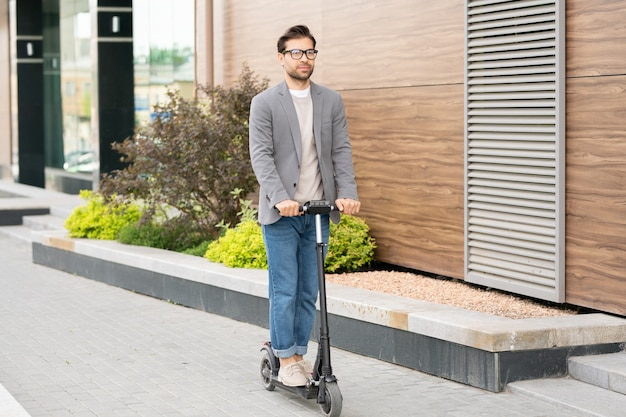 Jovem contemporâneo de jeans, pulôver e jaqueta cinza andando de scooter em ambiente urbano