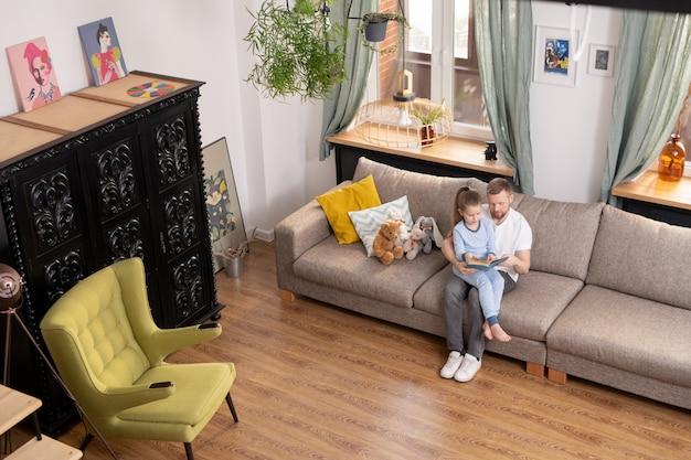 Jovem contemporâneo segurando sua adorável filhinha de joelhos enquanto lê um livro de contos de fada para ela na sala de estar