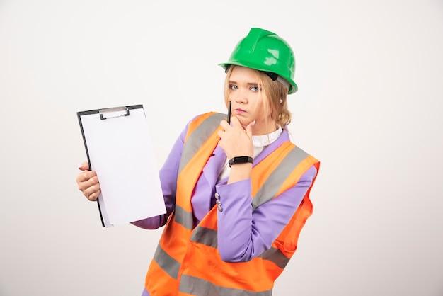 Jovem contratante feminino com capacete verde e prancheta na parede branca.