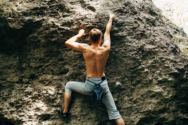 Jovem corajoso sobe a falésia