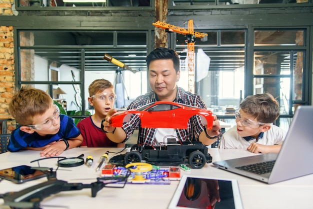 Jovem coreano de engenheiro eletrônico com crianças pequenas, usando a chave de fenda para desmontar a máquina robótica na mesa da escola moderna. câmera lenta