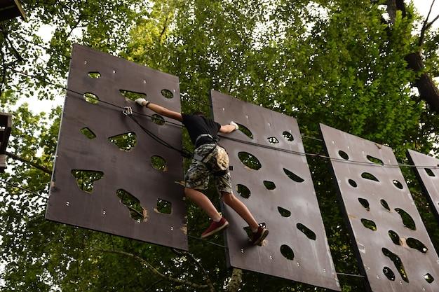 Jovem corre uma pista de obstáculos de árvore em árvore em um parque de cordas