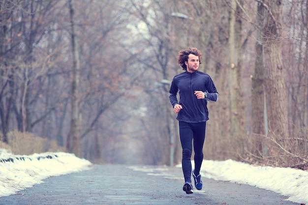 Jovem corredor correndo no parque na primavera, outono na natureza.