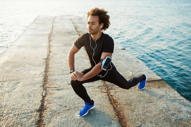 Jovem corredor de pele escura com belo corpo em forma, aquecendo os músculos antes do treino cardiovascular de treinamento de força.