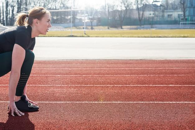 Jovem corredor em roupas esportivas se prepara para a arrancada na linha de largada na pista do estádio revestida de vermelho em um dia ensolarado