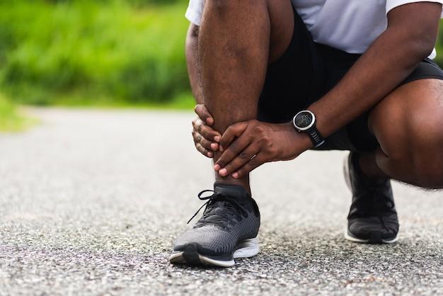 Jovem corredor esportivo negro usa relógio nas mãos nas articulações e dor nas pernas por causa da torção do tornozelo quebrado durante a corrida