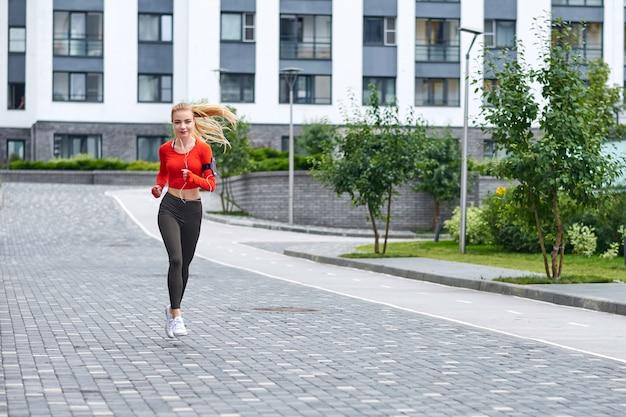 Jovem corredor feminino com capuz está correndo na rua da cidade
