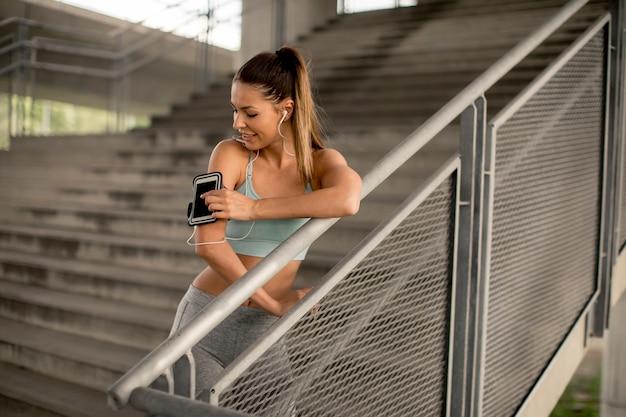 Jovem corredor feminino descansando nas escadas