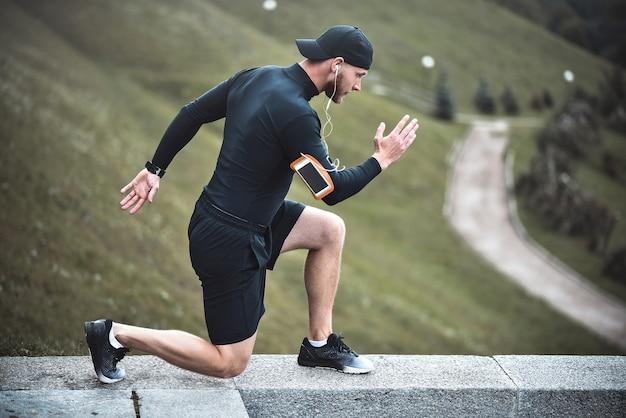 Jovem corredor masculino caucasiano com rastreador de aptidão anexado ao braço faz aquecimento antes de correr.