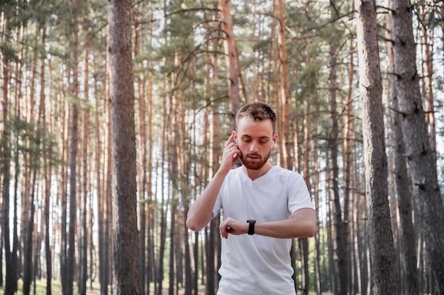 Jovem corredor masculino usando tecnologia moderna durante o exercício de corrida cross-country.