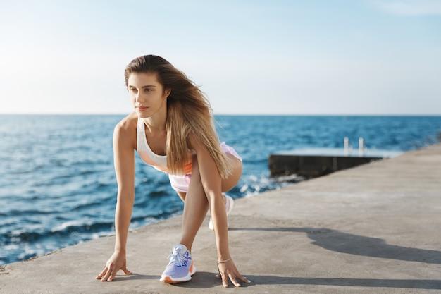 Jovem corredora motivada em forma deslumbrante, melhorando a técnica de início de corrida em pé, parte inferior do corpo do cais