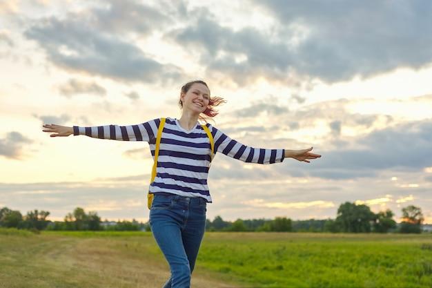 Jovem correndo com mochila amarela, com as mãos abertas