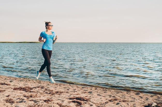 Jovem correndo. corredor de mulher correndo na praia de areia do verão ensolarado. treino perto da costa do mar oceano. linda garota em forma. etnia caucasiana modelo fitness ao ar livre. exercício de perda de peso. corrida.