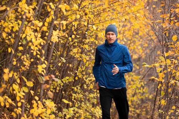 Jovem correndo na trilha na floresta