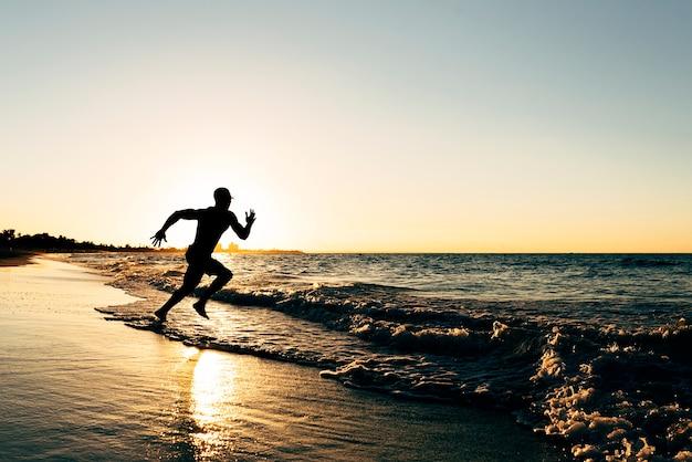 Jovem correndo para a praia. atitude feliz.