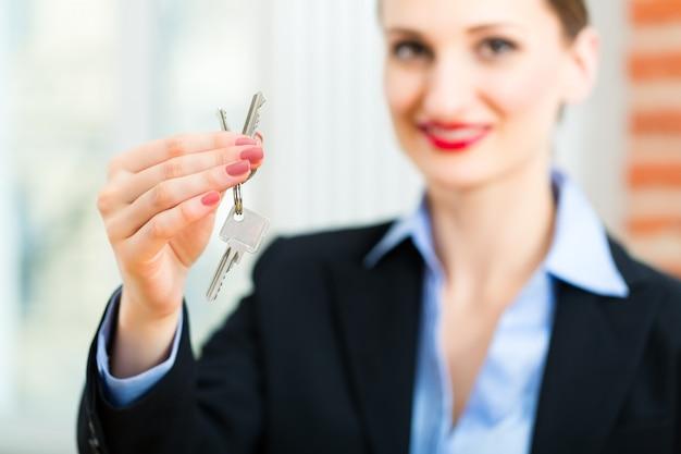 Jovem corretor de imóveis é com chaves em um apartamento