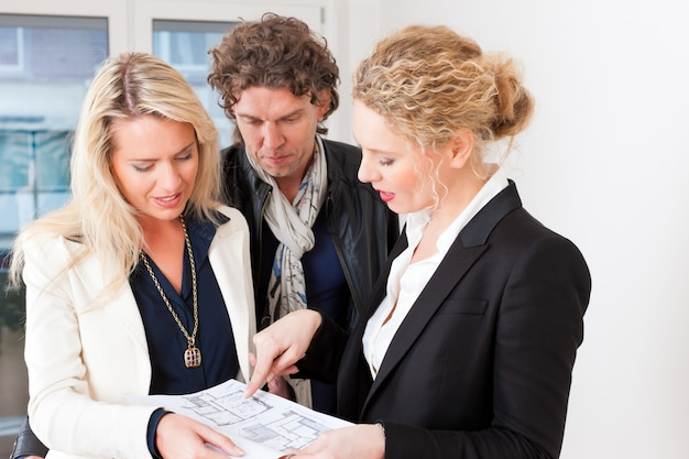 Jovem corretor de imóveis explica contrato de locação para casal