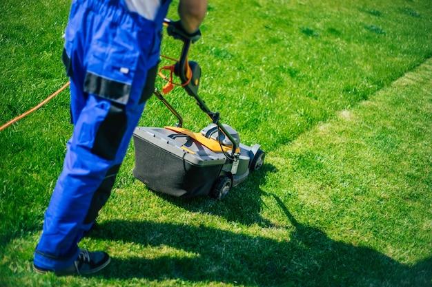 Jovem corta a grama usando um cortador de grama elétrico em um terno de trabalhador especial perto de uma grande casa de campo no quintal