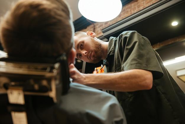 Jovem cortando cabelo barba de cabeleireiro enquanto está na cadeira de barbearia.