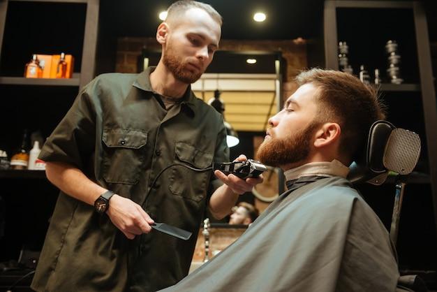 Jovem cortando cabelo barba de cabeleireiro enquanto está sentado na cadeira de barbearia.