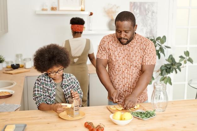 Jovem cortando limão enquanto o filho rala queijo