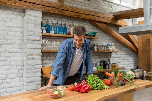 Jovem cortar legumes na cozinha e preparar uma refeição saudável