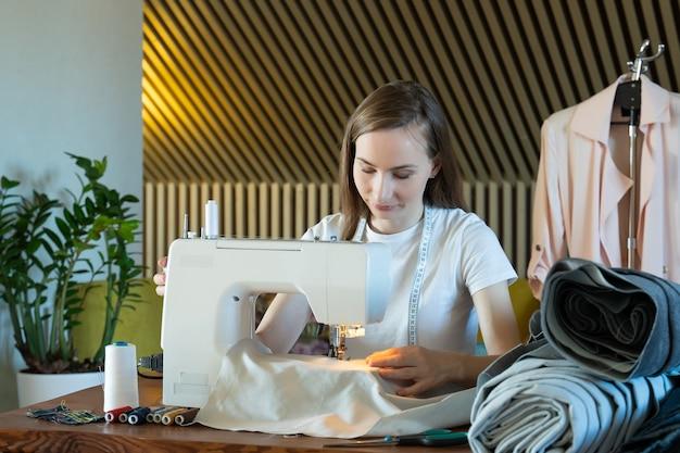 Jovem costureira costura em uma máquina de costura sentada a uma mesa