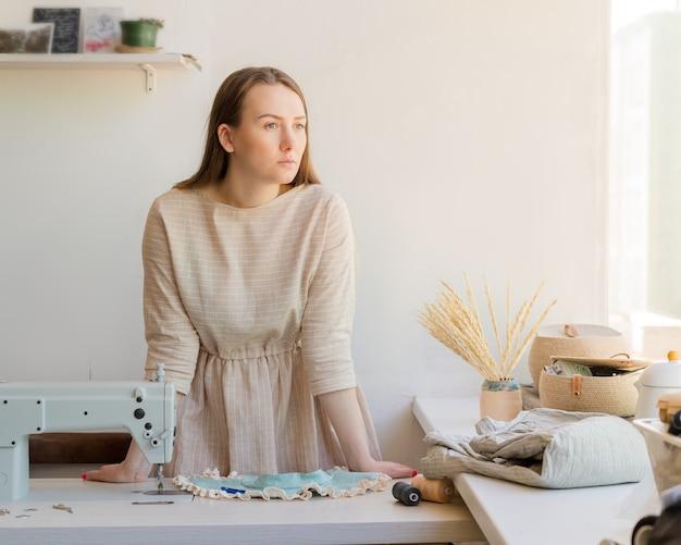 Jovem costureira em pé perto do local de trabalho em um ateliê de moda olhando para longe com olhar pensativo