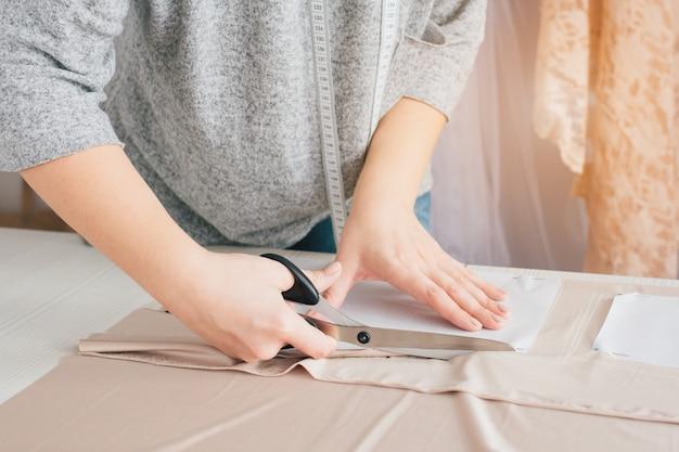 Jovem costureira faz roupas cortando tecido