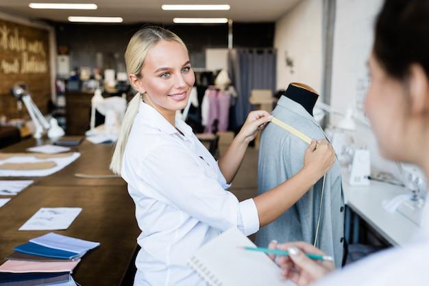 Jovem costureira loira sorridente olhando para a colega durante uma conversa enquanto tirava medidas da jaqueta no manequim