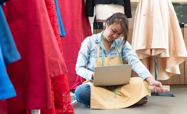 Jovem costureira usando um laptop