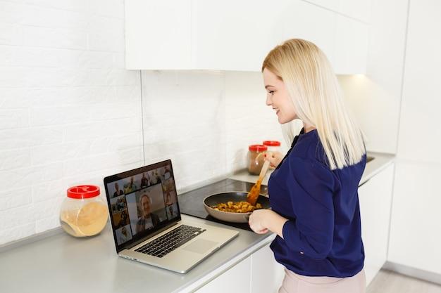 Jovem cozinha em frente ao laptop aberto e videochat na cozinha