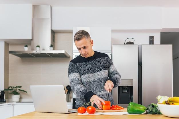 Jovem cozinhando e preparando uma refeição saudável em sua cozinha e vendo receitas no caderno