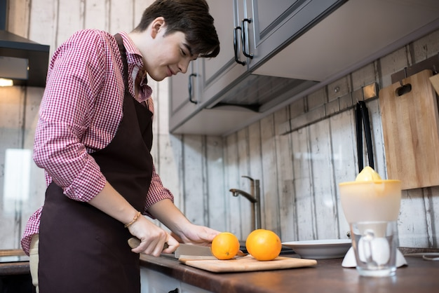 Jovem cozinhando em casa
