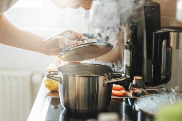 Jovem cozinhar alimentos frescos em casa e abrir a tampa da panela fumegante.