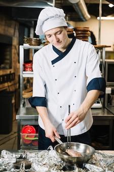 Jovem cozinhar fritar a carne na panela no fogão
