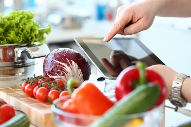 Jovem cozinhar salada fresca e usando computador tablet