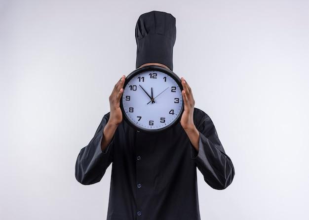 Jovem cozinheira afro-americana com uniforme de chef fecha rosto com relógio isolado no fundo branco com espaço de cópia