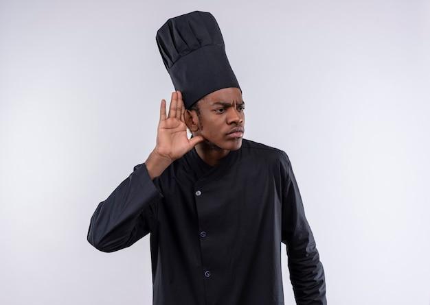 Jovem cozinheira afro-americana irritada com gestos de uniforme de chef não consegue ouvir o sinal da mão isolado no fundo branco com espaço de cópia