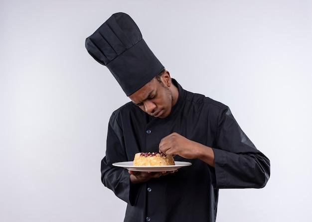 Jovem cozinheira afro-americana irritada com uniforme de chef segura e olha para bolo no prato isolado no fundo branco com espaço de cópia